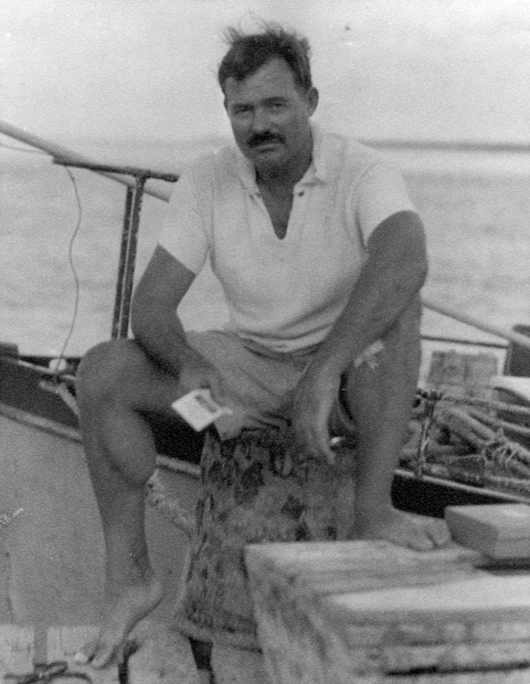 EH6670P   1930sErnest Hemingway sitting on a dock next to the Pilar, 1930s.  Photographer unknown in the Ernest Hemingway Collection of the John F. Kennedy Presidential Library and Museum, Boston.