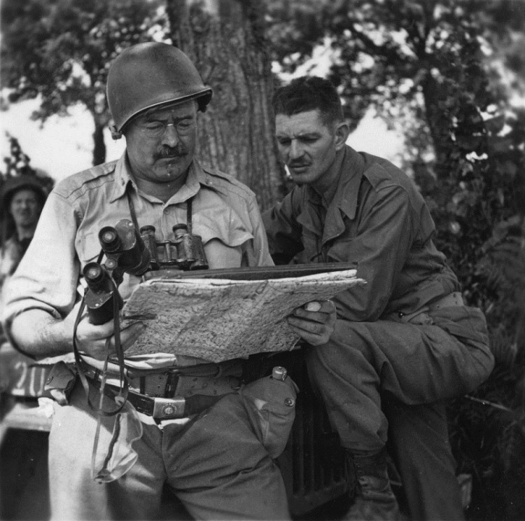 EH6891P Ernest Hemingway with soldier looking at a map in World War II.  Photograph coopyright unknown and held in the Ernest Hemingway Collection at the John F. Kennedy Presidential Library and Museum, Boston.