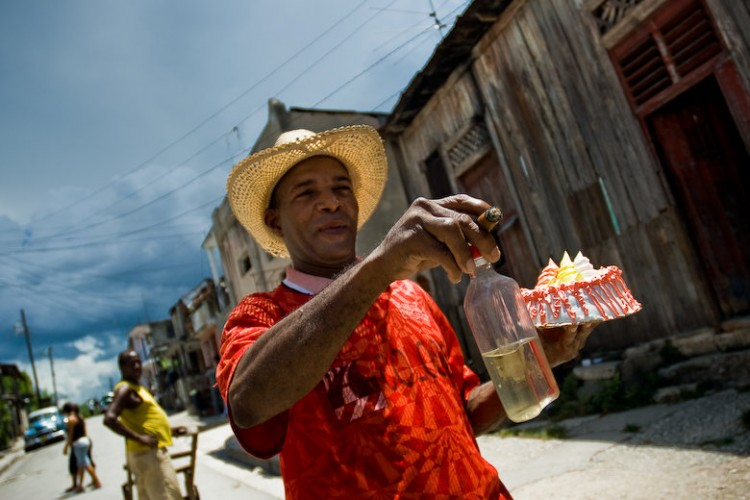 A Cuban man hurrying for a fiesta, holding a bottle of rum, smoking a cigar and carrying a sweet cake in his hand, Santiago de Cuba, Cuba, 3 August 2008. Although the overall situation in Cuba is tough and life is challenging there, Cubans never forget to celebrate, to call for a fiesta. About 50 years after the national rebellion led by Fidel Castro and adopting the communist ideology shortly after the victory, the Caribbean island of Cuba is the only country in Americas having the socialist political system. Although the Cuban state-controlled economy has never been developed enough to allow Cubans living in social conditions similar to the US or to Europe, mostly middle-age and older Cubans still support the Castro Brothers' regime and the idea of the Cuban Revolution. Since the 1990s Cuba struggles with chronic economic crisis and mainly young Cubans call for the economic changes.
